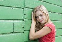 Retrato de jovem mulher inclinada em uma fachada de madeira verde — Fotografia de Stock