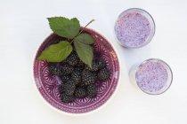 Tigela de folha de amoras frescas e dois copos de smoothie de amora — Fotografia de Stock