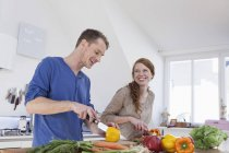 Young couple preparing food in kitchen — Stock Photo