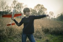 Boy playing with toy aeroplane — Stock Photo