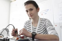 Young woman working on optical sensor in an electronic workshop — Stock Photo