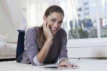 Женщина дома лежит на ковре и с помощью планшетного компьютера — стоковое фото