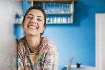 Retrato da jovem mulher feliz encostada à geladeira em sua cozinha — Fotografia de Stock