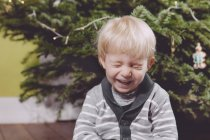 Laughing toddler under Christmas tree at home — Stock Photo