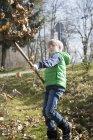Muchacho con rastrillo lanzando follaje otoñal en el aire - foto de stock