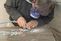 Gros plan du sculpteur travaillant sur la pierre tombale en atelier — Photo de stock