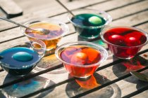Close-up of colorful Easter eggs in glass bowls with dyes on wooden table — Stock Photo