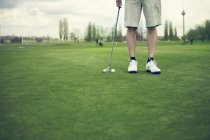 Recadrée tir du joueur de golf masculin debout à l'aire de jeux avec golf club — Photo de stock