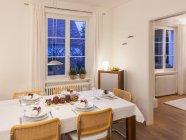 Столовая с праздничной накрытый стол вечером — стоковое фото