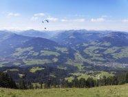 Austria, Tyrol, Kitzbuehel Alps, Brixen Valley with Hopfgarten town and paraglider — Stock Photo