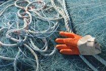 Francia, Bretagne, Finistere, Landeda, red de pesca con guante de trabajo en el puerto - foto de stock