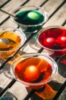 Elevated view of colorful Easter eggs in glass bowls with dyes on wooden table — Stock Photo