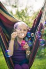 Portrait of smiling little girl blowing soap bubbles — Stock Photo