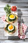 Fried eggs and spinach on toast with tomatoes — Stock Photo