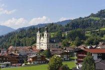 Austria, Tirol, Kitzbuehel Alpes, Brixen Valley, Hopfgarten con iglesia de san Leonardo, paisaje natural verde sobre fondo - foto de stock