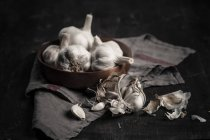 Garlic cloves and bulbs on dark background with cloth — Stock Photo