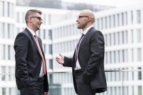 Two businessmen under discussion at modern building — Stock Photo