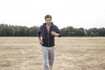 Man wearing hooded jacket jogging on field — Stock Photo