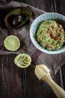 Чаша гуакамоле з стиснув вапна і видовбані половина з авокадо на кухонне рушник — стокове фото