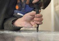 Primer plano de escultor trabajando en lápida en taller - foto de stock