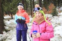 Две девочки-подростки в красочной зимней одежде стоят на природе — стоковое фото