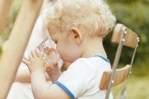Acqua potabile del bambino sulla sedia in un giardino — Foto stock