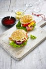 Two prepared burgers, mustard and ketchup on wooden ground — Stock Photo