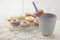 Glaseado rosquillas al horno con taza colocada en el paño blanco, primer plano - foto de stock