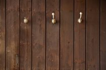 Three coat hooks on wooden wall — Stock Photo