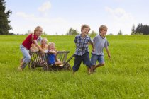 Group of children playing with hand cart — Stock Photo