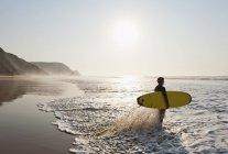 Серфер на пляже в живописный закат — стоковое фото