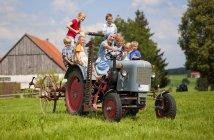 Femme avec groupe d'enfants assis sur un vieux tracteur devant la ferme — Photo de stock