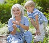 Зрелая женщина и мальчик, осмотр морковь в саду — стоковое фото