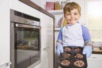 Garçon cuisson gâteaux tasse dans le plateau, portrait — Photo de stock
