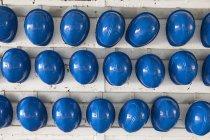 Filas de cascos de seguridad azules en estantes - foto de stock