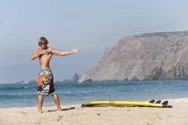 Серфер, растяжения на пляже — стоковое фото