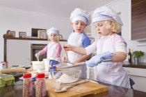 Filles et garçon tamiser farine dans un bol ta cuisine — Photo de stock