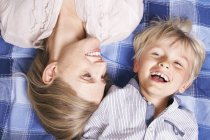 Smiling Mother and son lying on blanket — Stock Photo