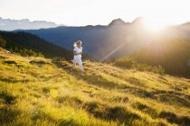 Austria, Salzburg County, Young woman running in alpine meadow — Stock Photo
