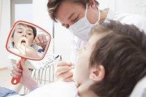 Стоматолог следственным маленького пациента — стоковое фото