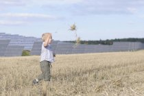 Boy running in grass, solar panels in background — Stock Photo