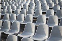 Rows of empty plastic chairs on stadium — Stock Photo