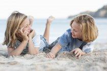 Діти, що лежить в піску на пляжі — стокове фото