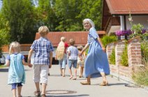 Mature woman with children dancing on street — Stock Photo