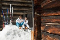 Young couple sitting with drinks in front of alpine hut in Salzburg, Austria — Stock Photo
