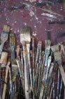 Variety of used paintbrushes on shabby background — Stock Photo