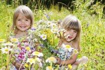 Girls picking flowers in summer meadow in Salzburg, Austria — Stock Photo