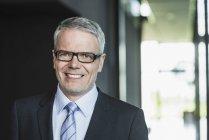Empresário de pé no prédio de escritórios, sorrindo — Fotografia de Stock