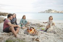 Spain, Mallorca, Friends grilling sausages at camp fire on beach — Stock Photo