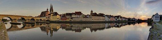 Alemanha, Bavaria, Regensburg, cidade velha e antiga ponte de pedra, atravessando o rio Danúbio ao pôr do sol — Fotografia de Stock